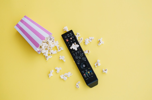 Image of a remote and popcorn cup with yellow background.